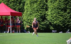 Kate Marano jumps onto the field playing lacrosse with her team.