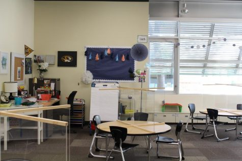 These classrooms in the Lower School often have bookshelves and other furniture, but in order to make room for distanced desks the furniture has been moved out and plexiglass has been put on the desks.