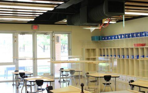 A classroom in the preschool has plexiglass barriers on each desk.