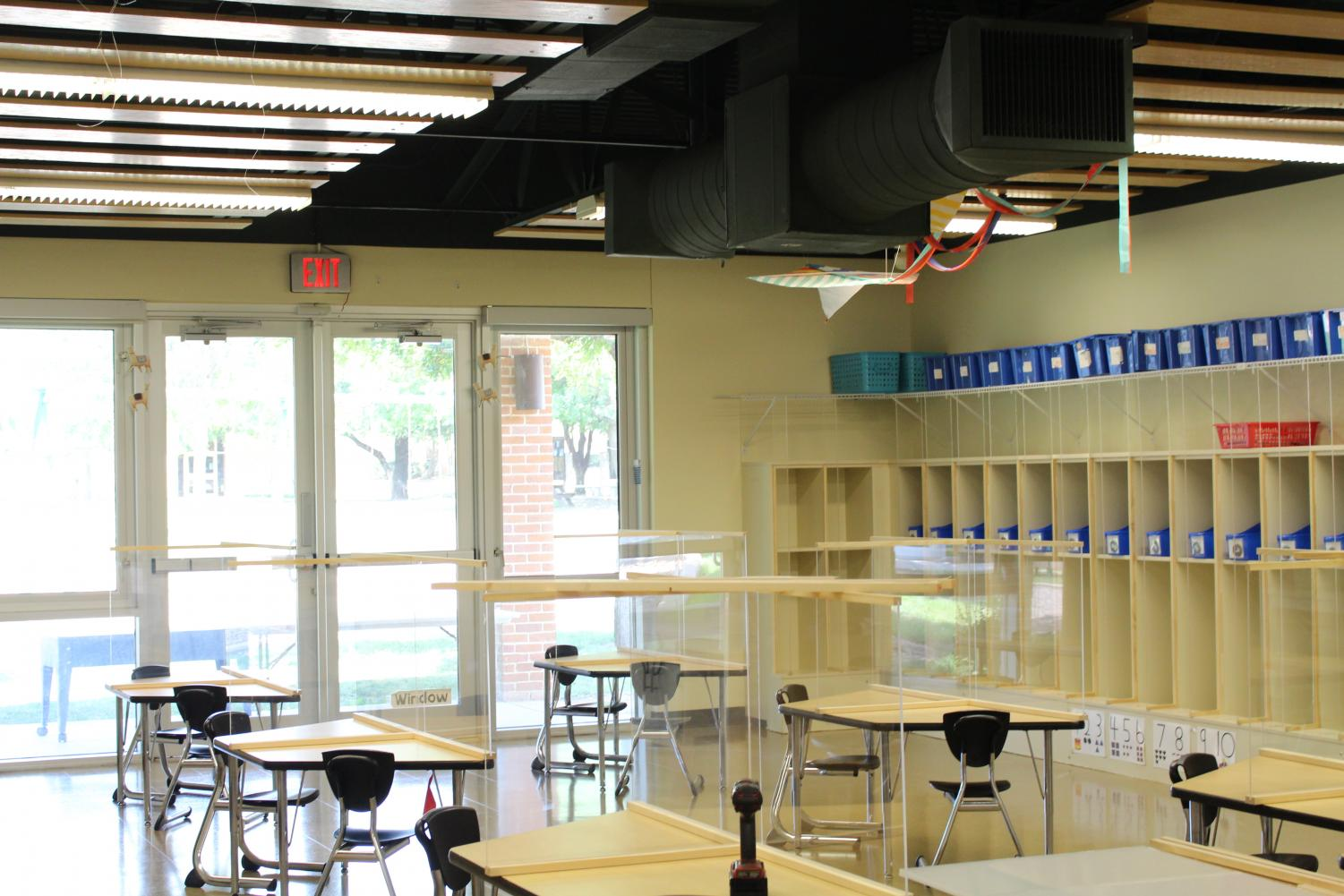 A classroom in the preschool has plexiglass barriers on each desk.