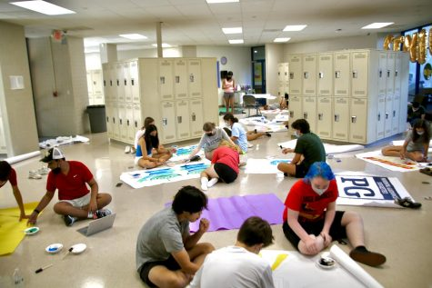 Students draw and paint homecoming decorations together on Sunday.